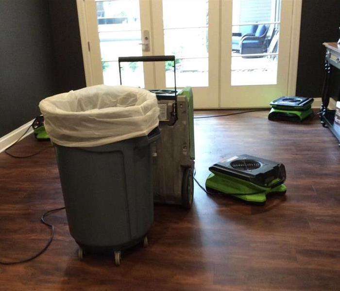 Room with hardwood floor, trash can with white bag.  1 Dehumidifier and 3 air movers on the floor to dry out the room.