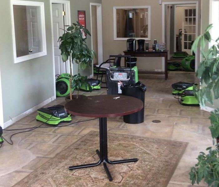 Office with vinyl flooring drying with SERVPRO drying equipment, plans, rug and tables throughout the room.